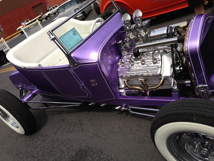 This vintage car looks great in its coat of shiny purple with the white upholstery.